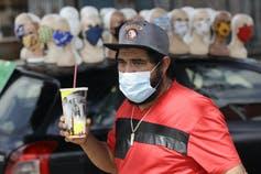 Un homme en chemise rouge, masqué, tient un soda devant un étalage de mannequins portant tous des masques